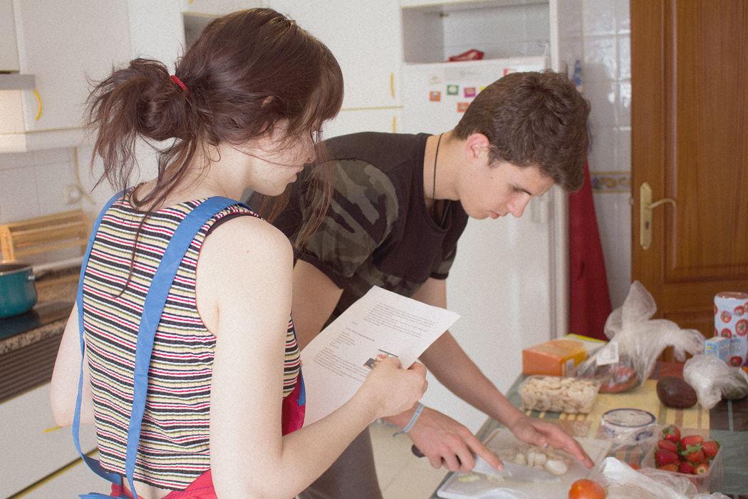 mozos tutelados preparando a comida seguindo unha receta